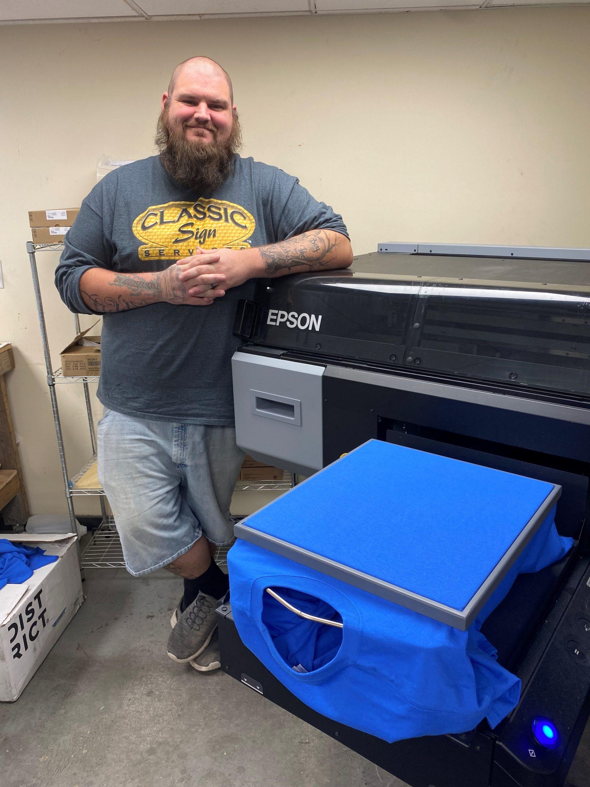 Brian Tidd standing beside the direct-to-garment (DTG) t-shirt printer